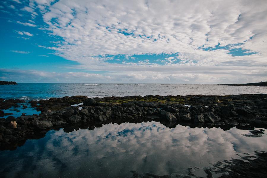 Hawaiian black sand beach and ocean on partly cloudy day