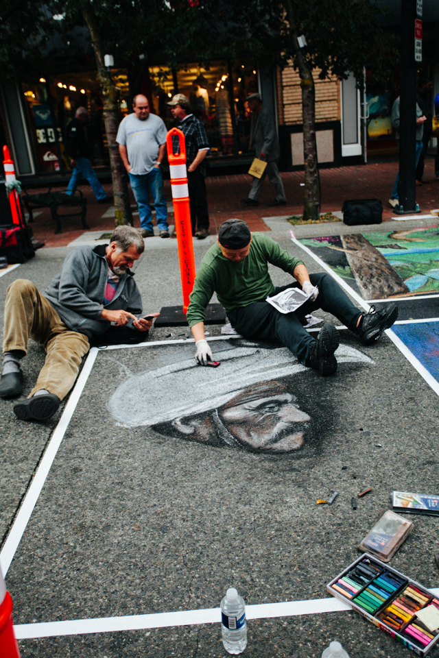 guy painting sidewalk with chalk black and white portrait at international chalk festival victoria canada