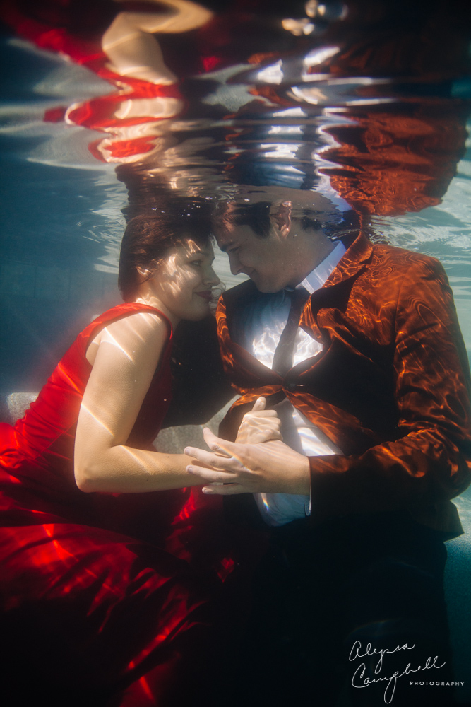lady in red dress with man in brown jacket underwater
