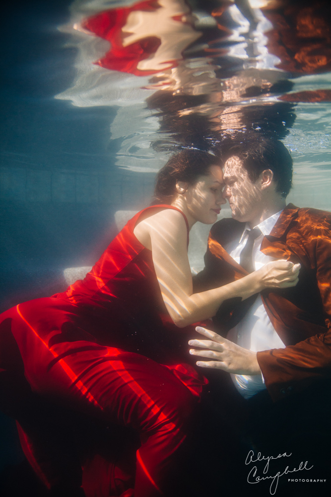 engagement photos underwater woman holding man in red dress and brown suit & tie