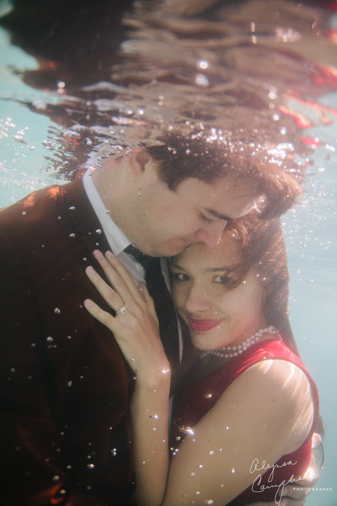 underwater engagement session woman with head on fiance's shoulder showing off ring