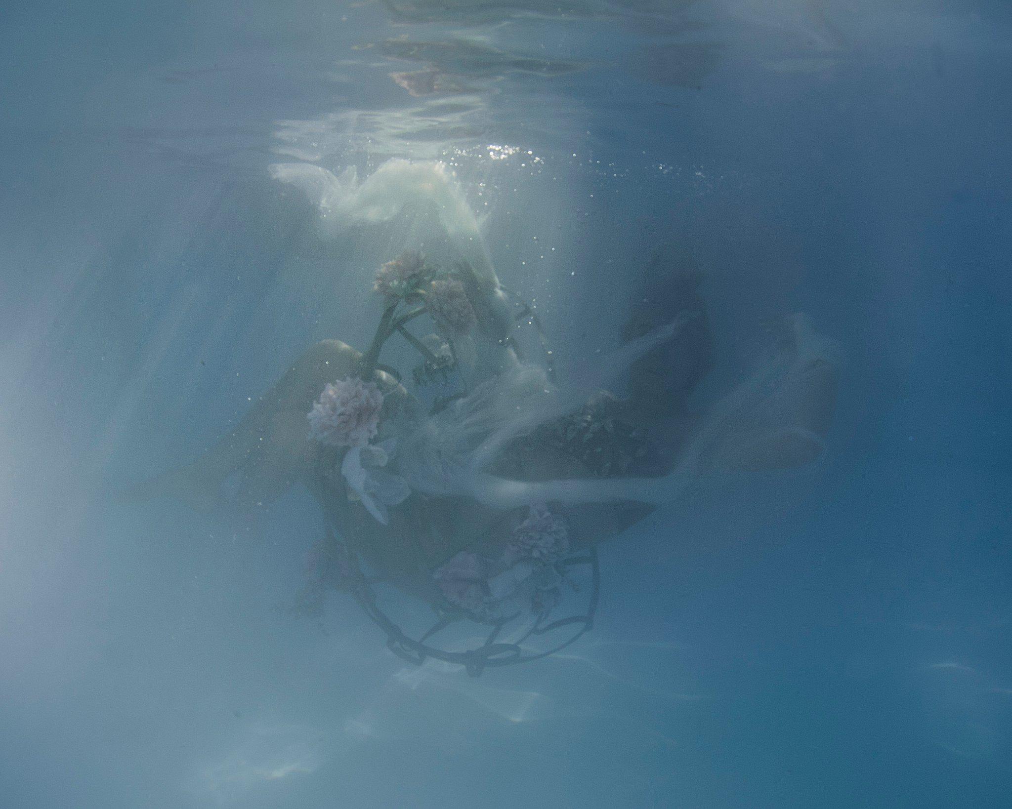ethereal underwater portrait of ballerina falling in water