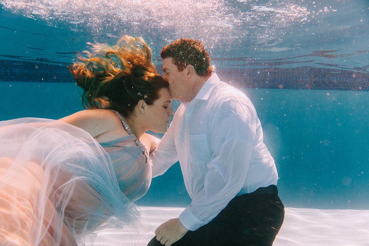 couple in formalwear underwater for unique creative underwater engagement session in Arizona