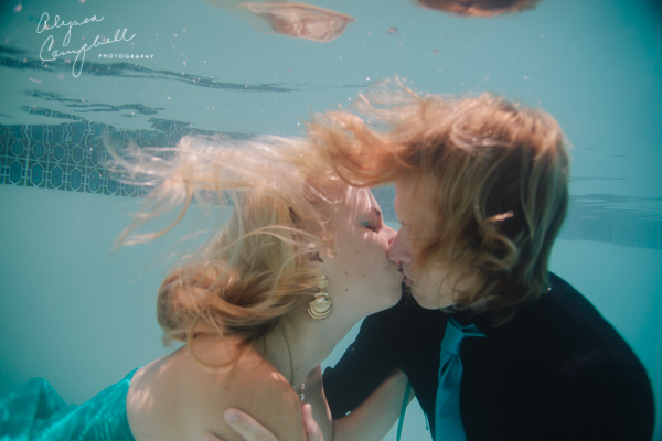 underwater engagement photo couple kissing underwater in pool