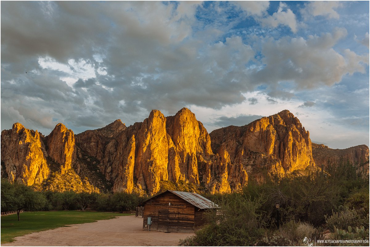 Saguaro Lake Guest Ranch Mesa, AZ with old western style barn & mountains lit by the setting sun