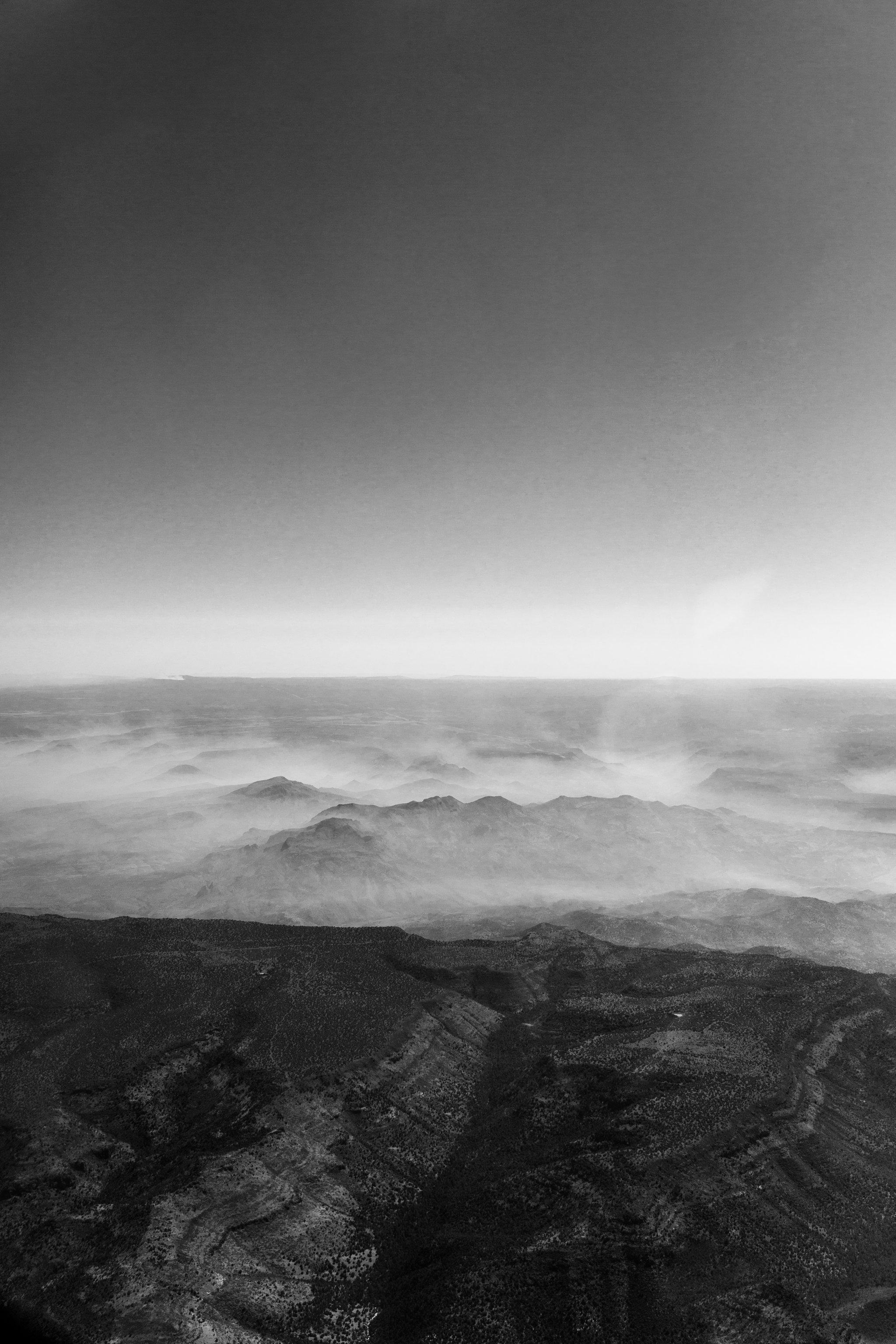 black and white photo of hazy Arizona mountains from a plane