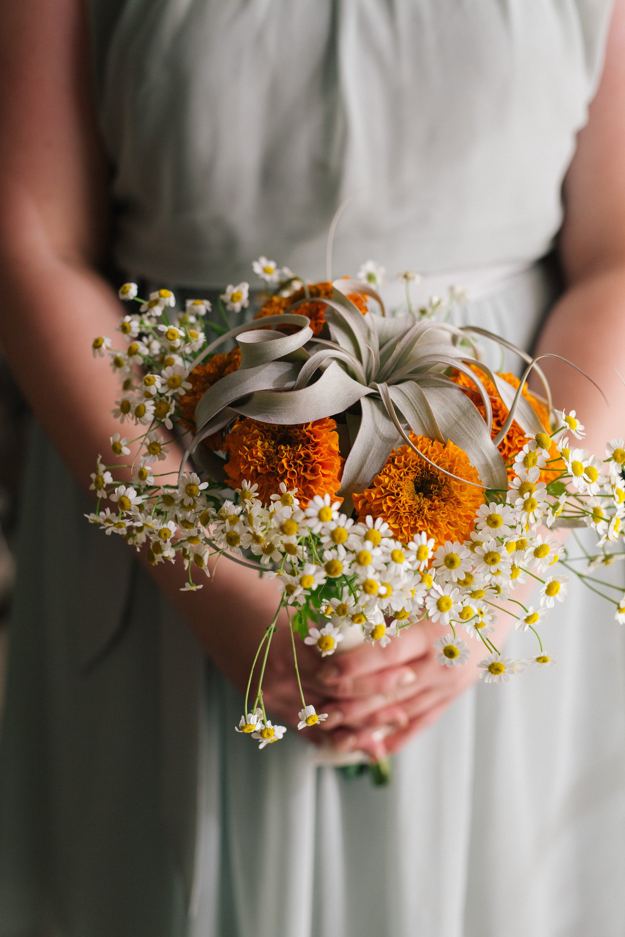 sage and orange bouquet with air plant
