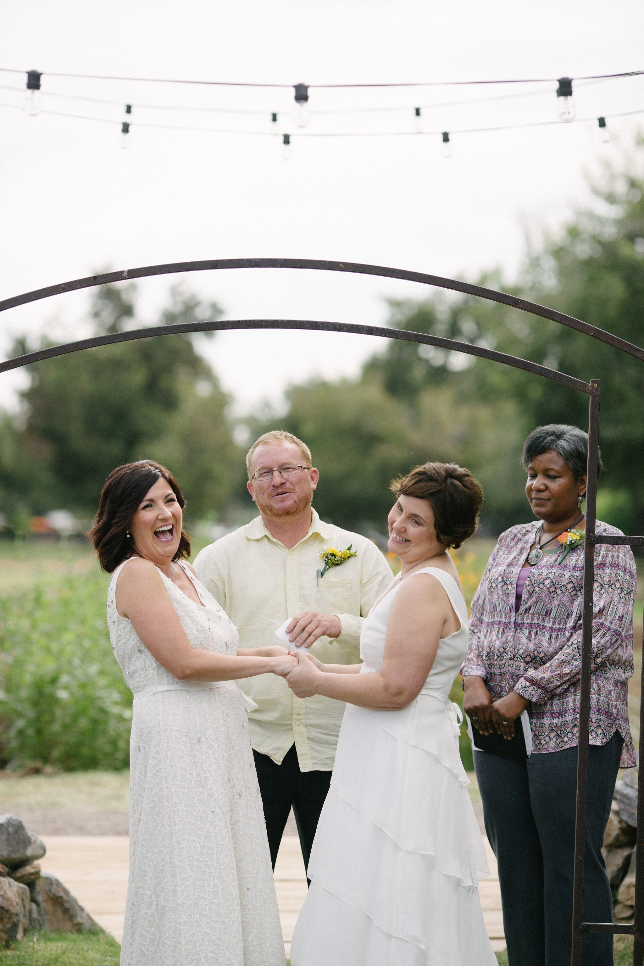 two brides laughing during Farm at South Mountain wedding ceremony by Arizona candid wedding photographer