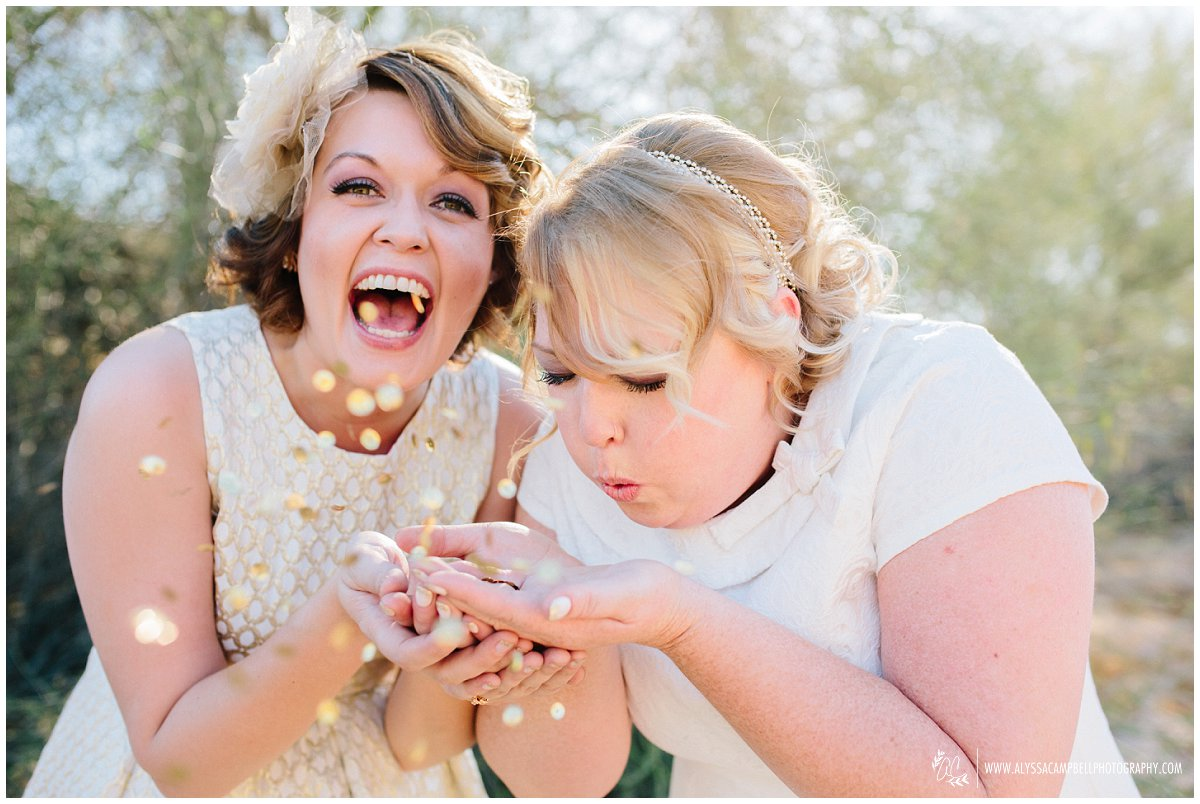 two brides blowing glitter happy genuine real emotional wedding photos in Arizona