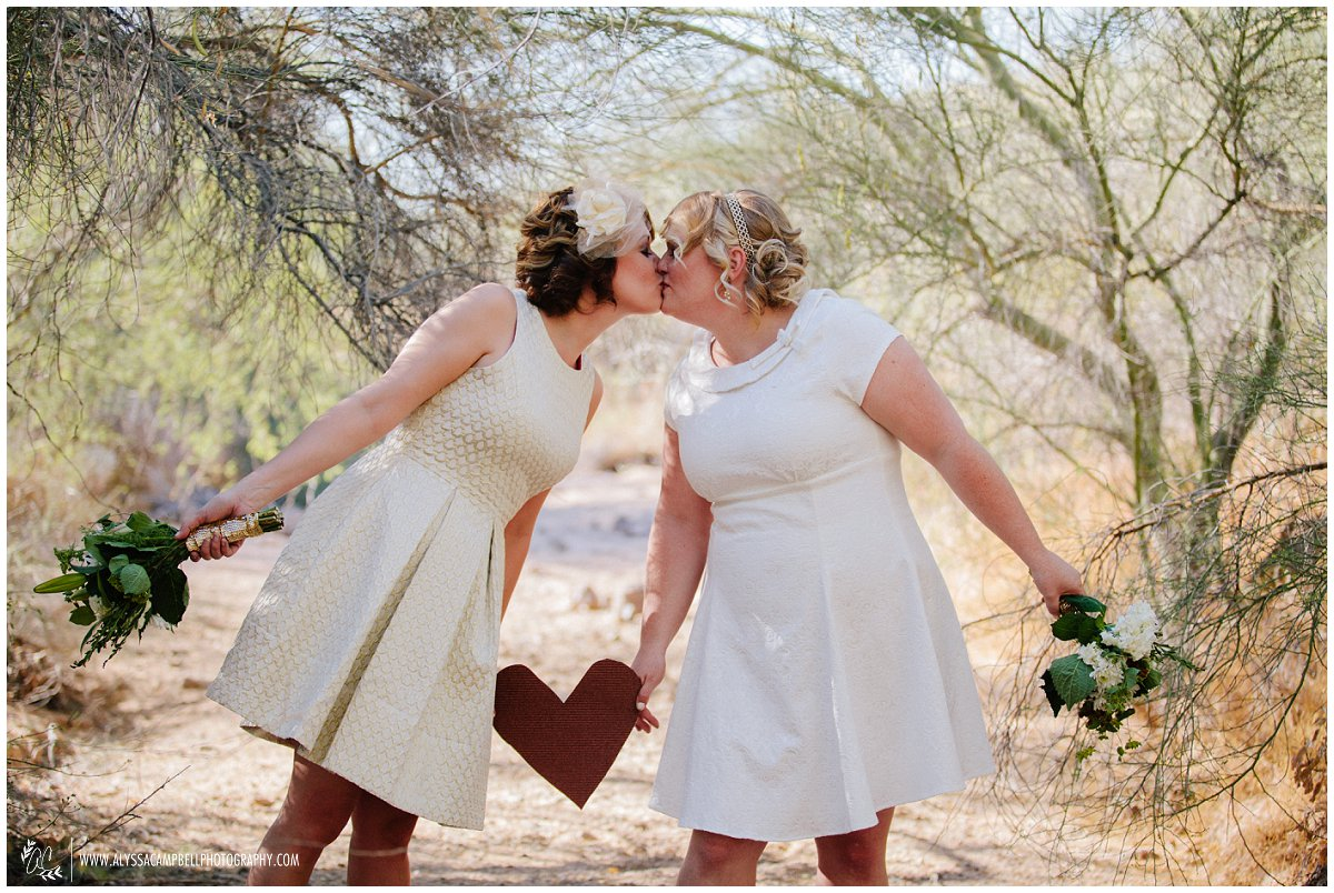 two brides kissing over a red heart in Phoenix AZ desert LGBT friendly Arizona wedding photographer