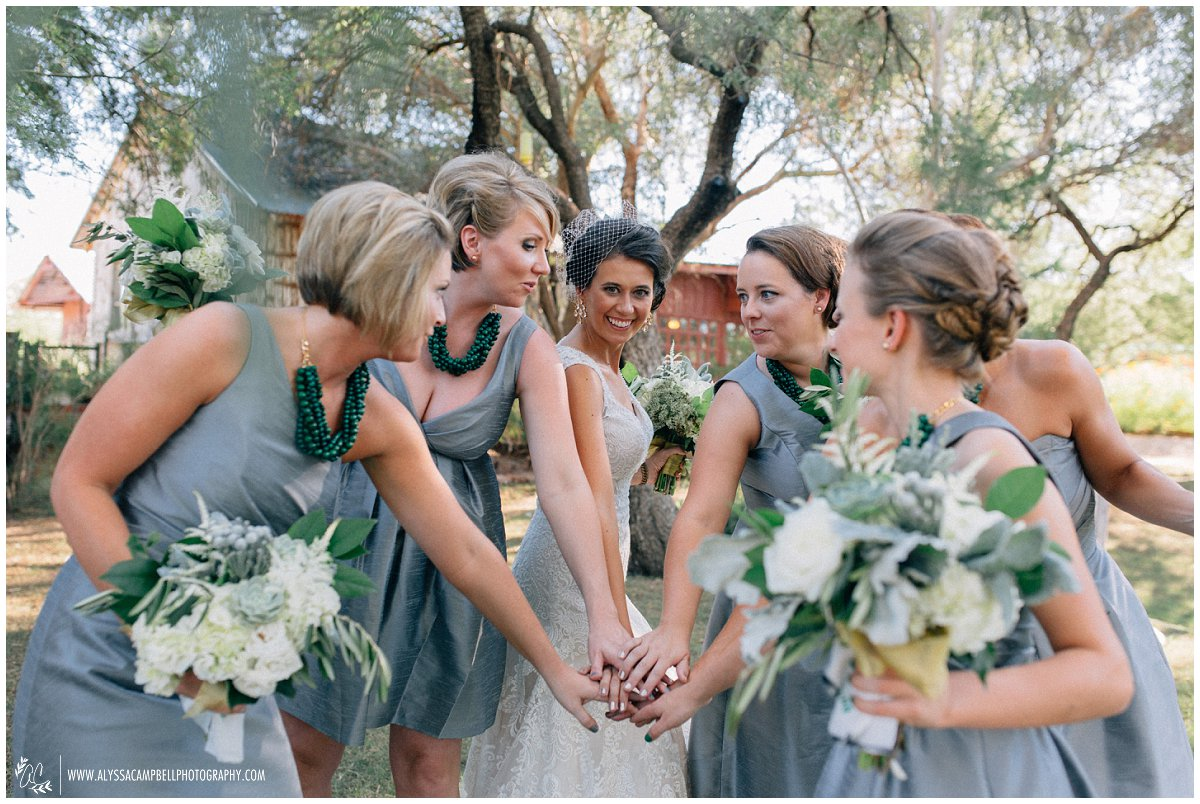 bride & bridesmaids with hands together at Windmill Winery elegant barn wedding