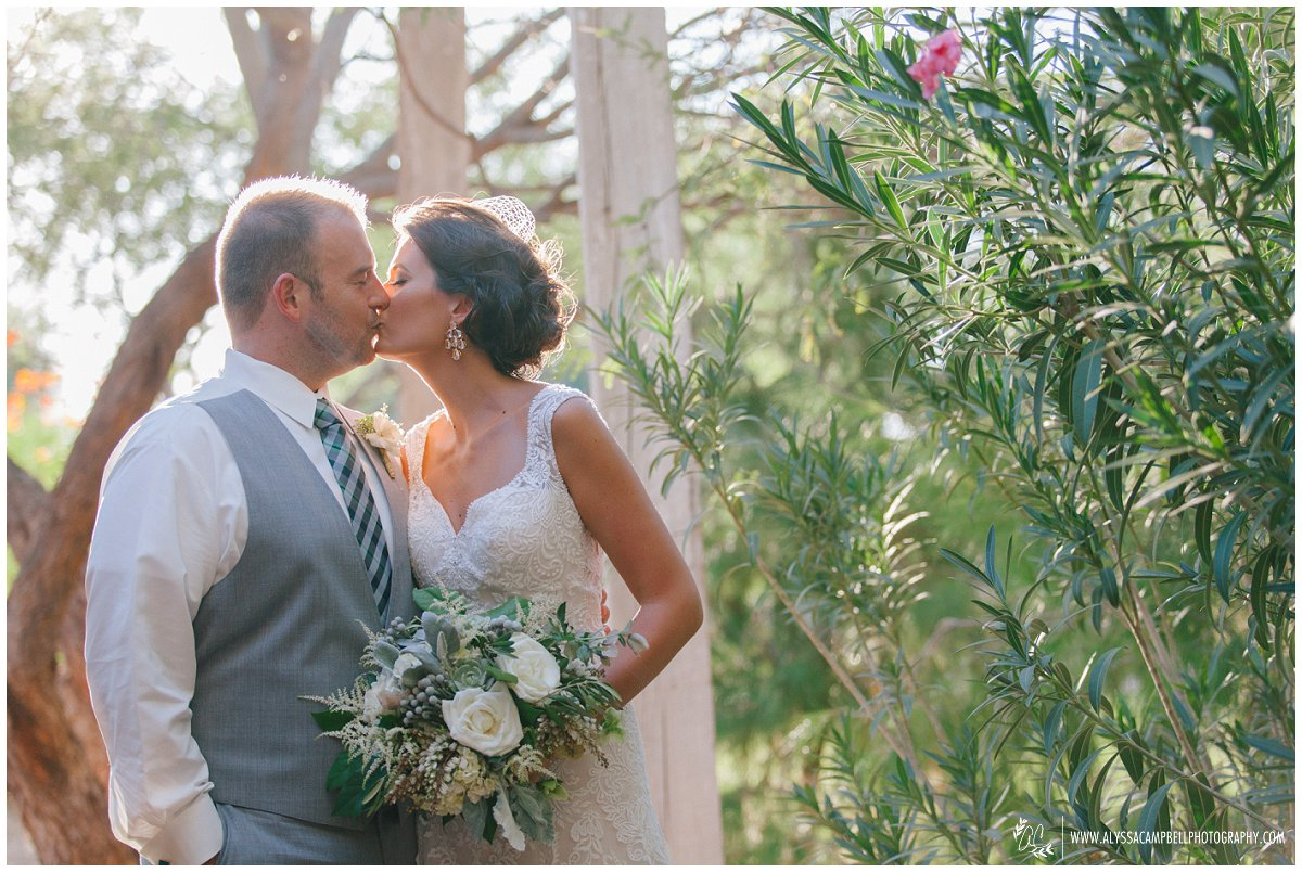 bride & groom kissing at Windmill Winery gardens