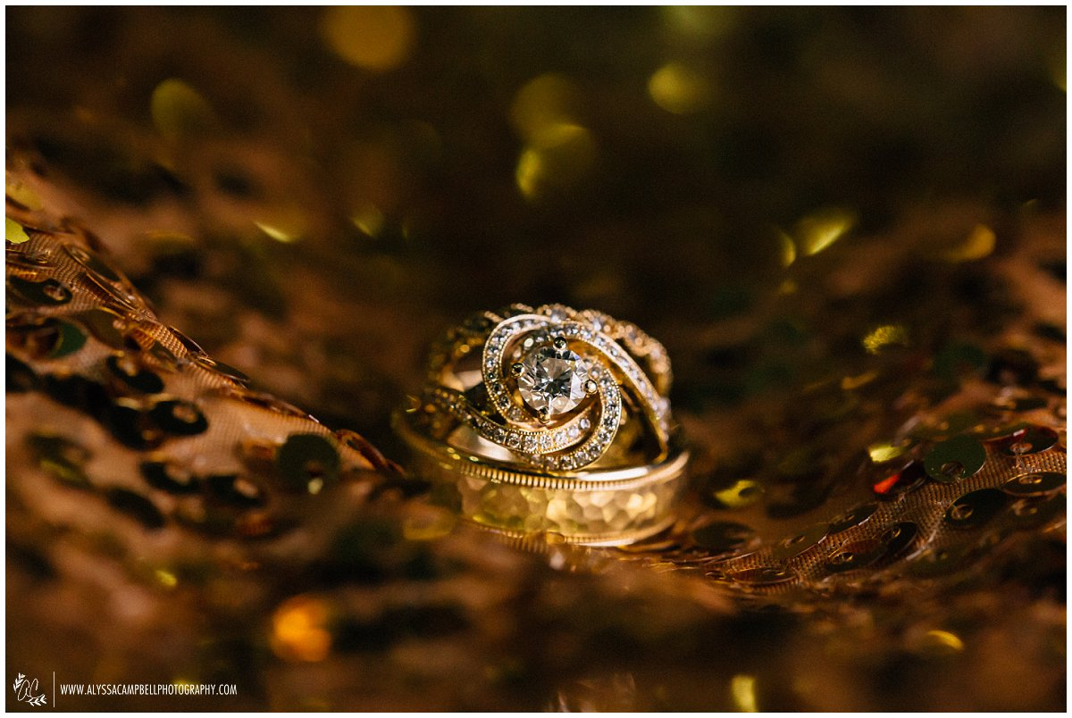gold rose shaped wedding ring on gold sequin backdrop