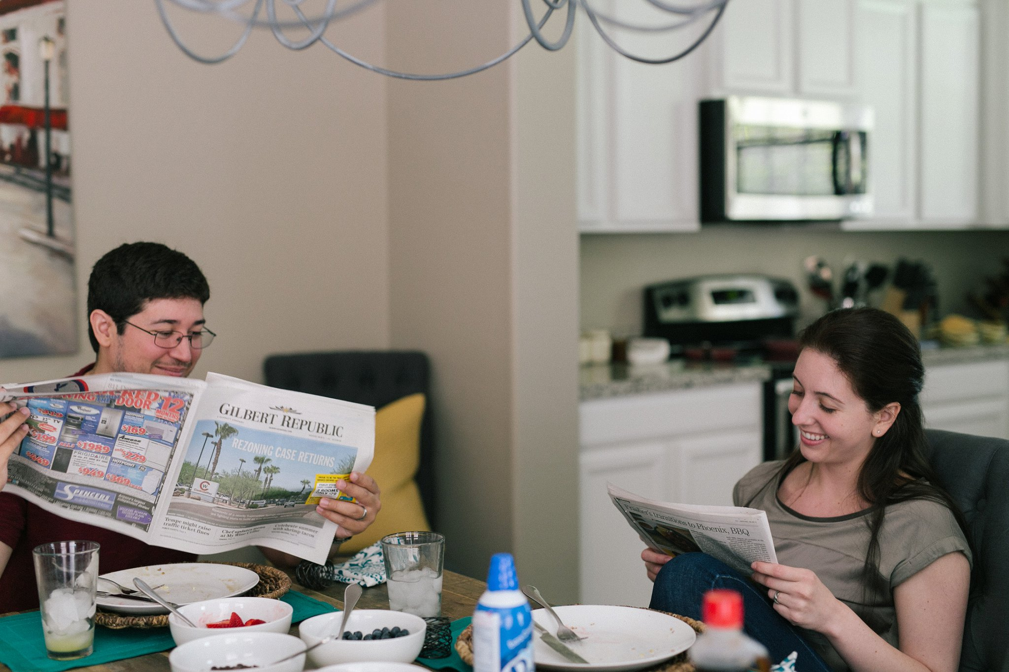 couple sitting at table reading newspaper smiling lazy Sunday engagement session