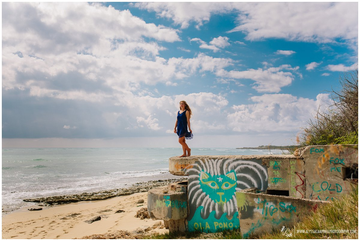 Oahu high school senior portrait of a girl standing on graffiti wall on the beach looking out into the ocean