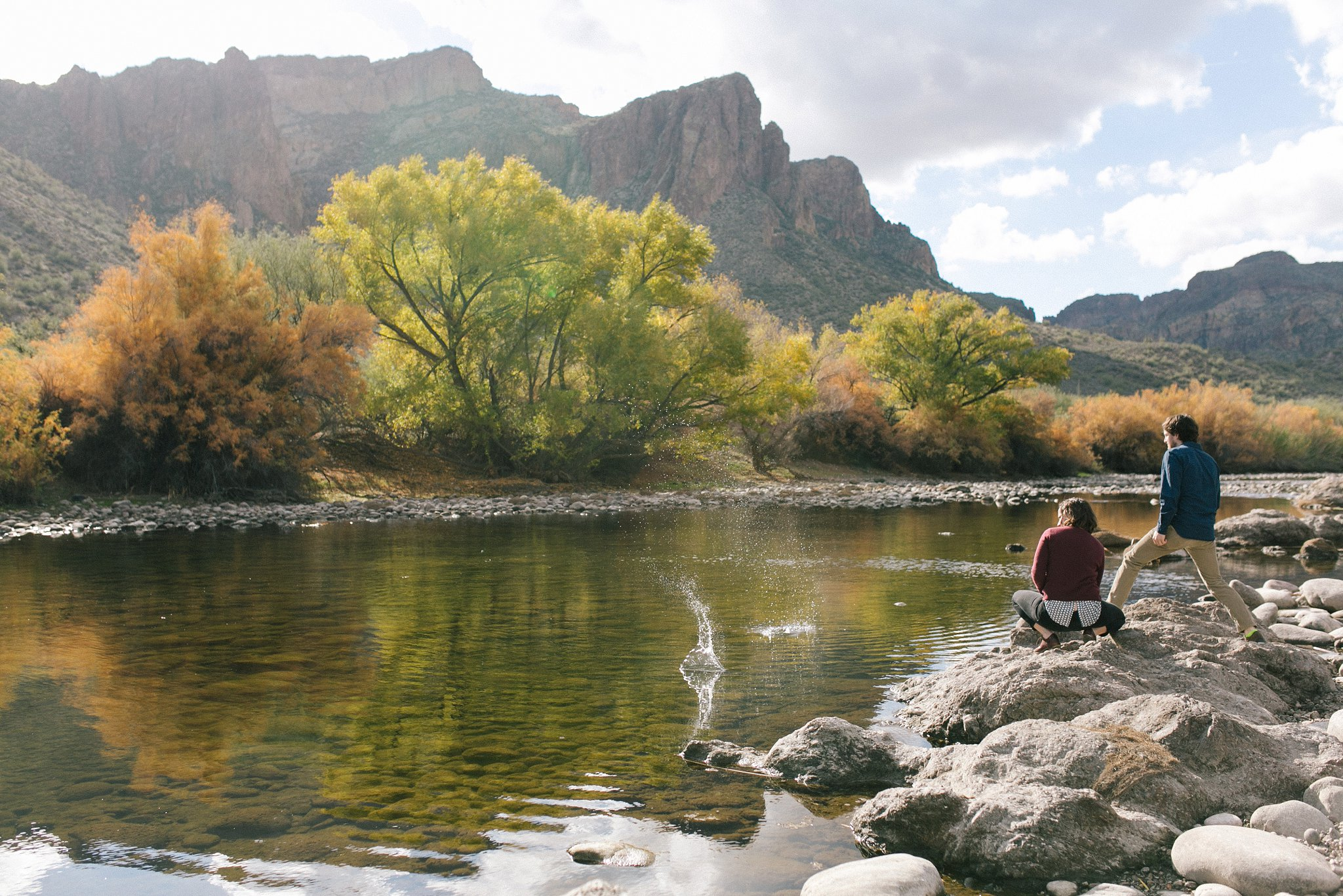 engagement session skipping rocks along Salt River & mountains in Arizona