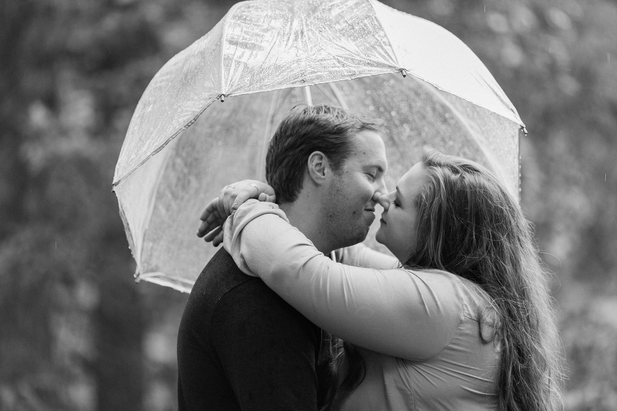 engagement photos in Payson Arizona in rain with clear umbrella