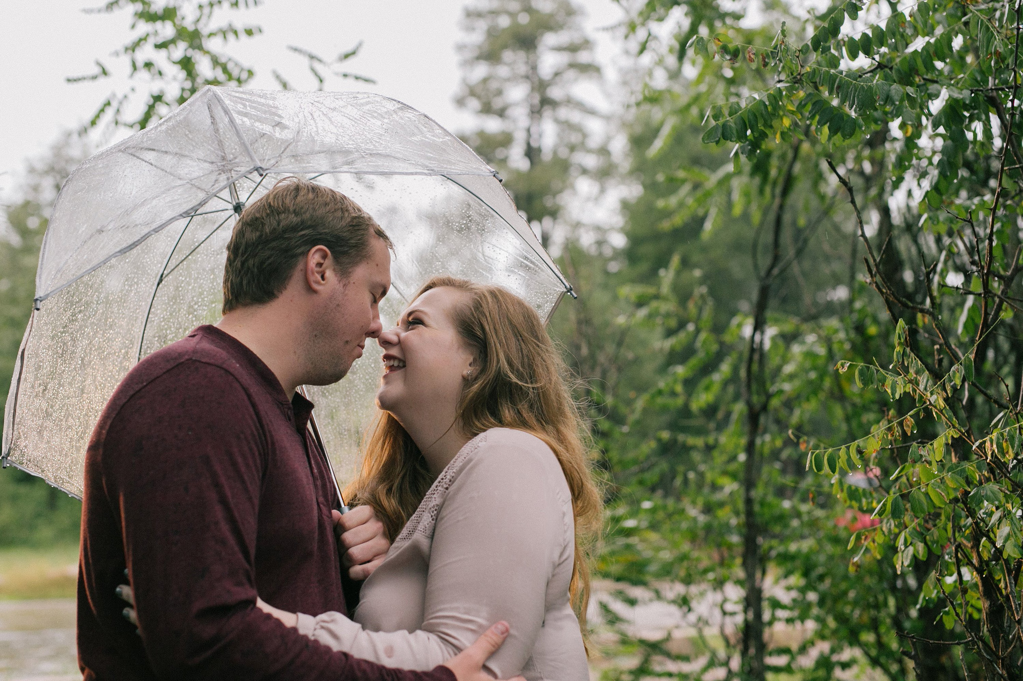 mogollon rim engagement session in the rain with clear umbrella laughing