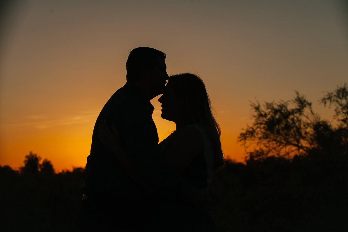 couple silhouetted at sunset in Papago Park engagement session
