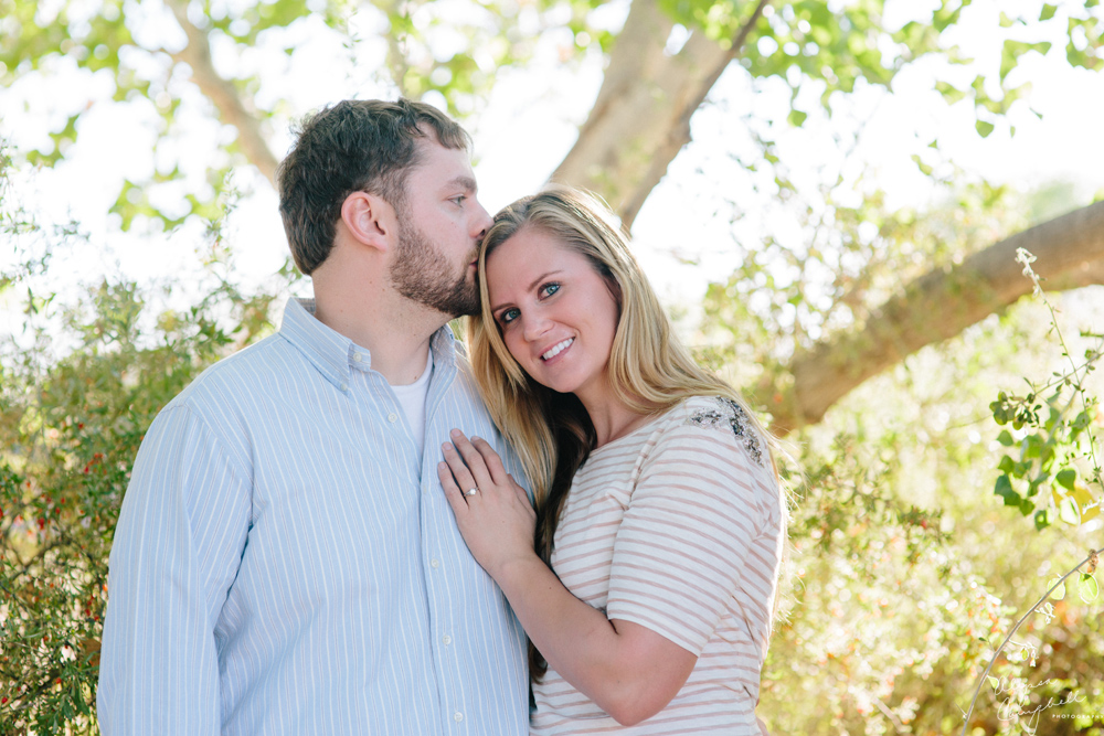 Guy kissing fiance on forehead in front of tree