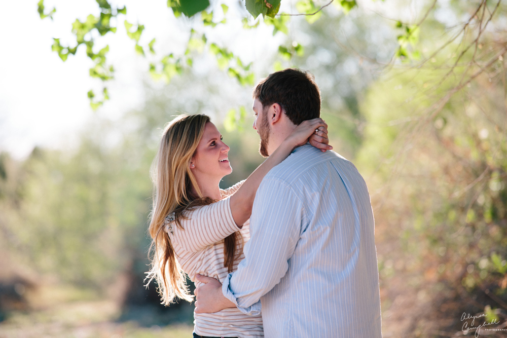 engaged couple dancing together beside a tree