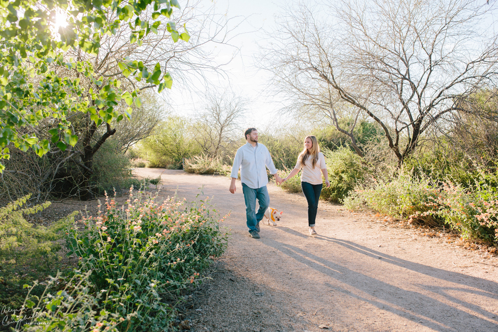 couple walking with dog along path with trees