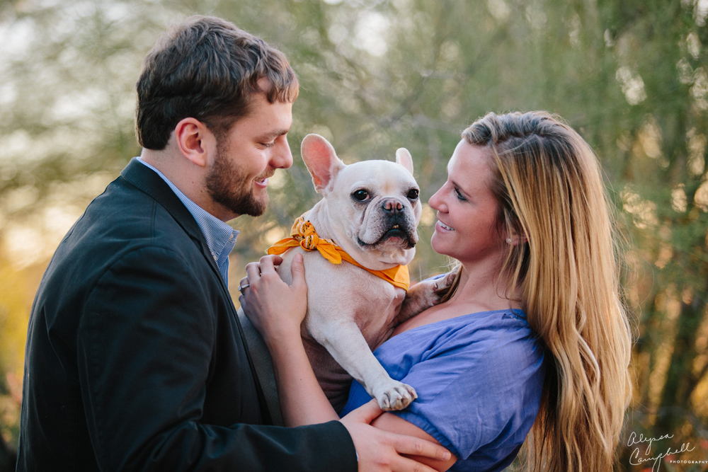 couple with French bulldog in arms laughing