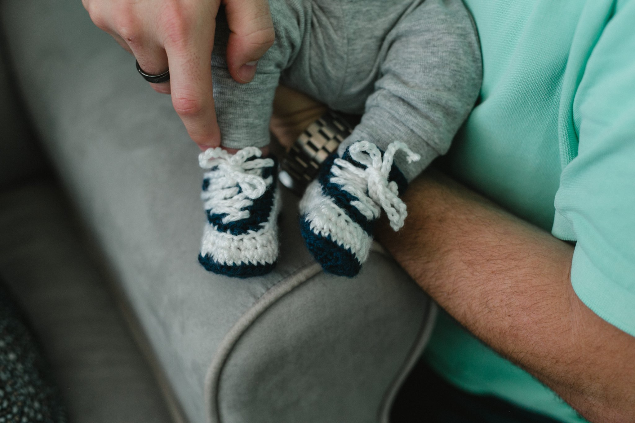 one month old baby with knitted wrestling shoes