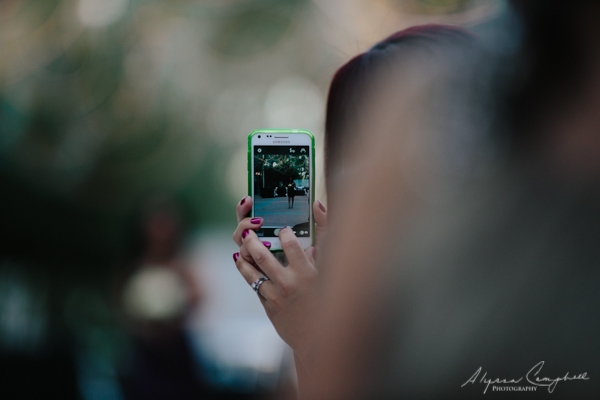 photo of phone with photo of someone walking down wedding aisle