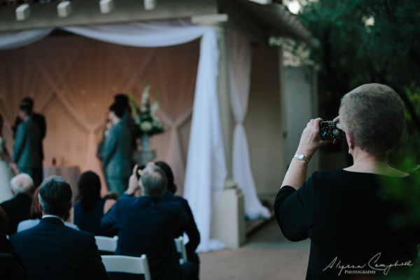 photo of two guests taking photos at wedding ceremony
