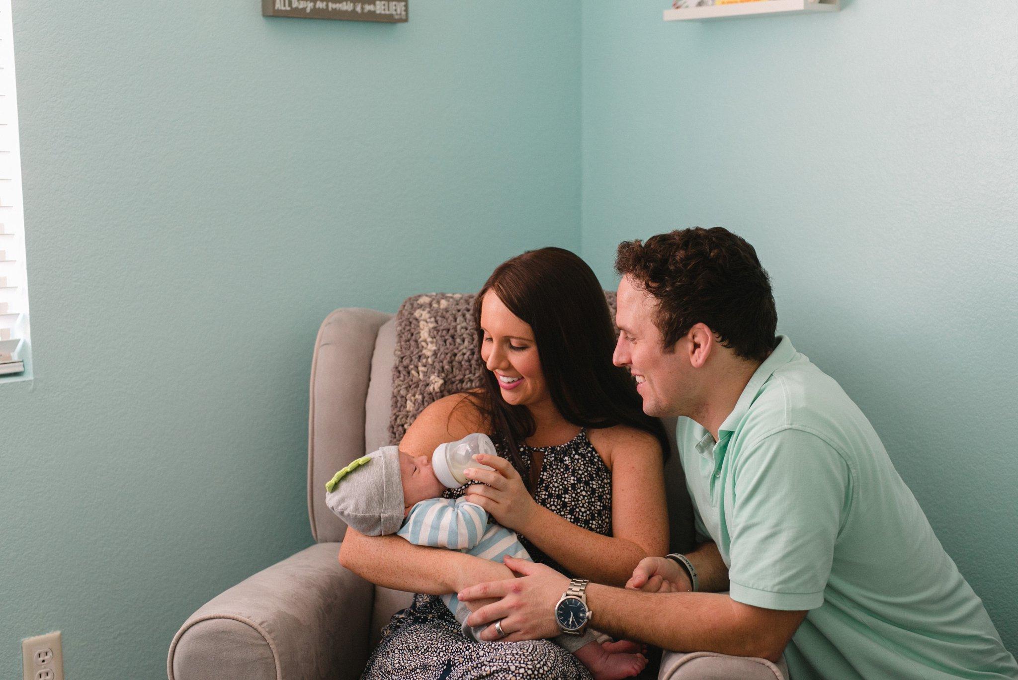 new parents bottle feeding son in blue nursery in Chandler AZ