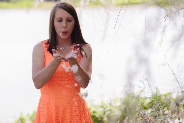 Arizona college senior girl portrait blowing dandelions in an orange dress
