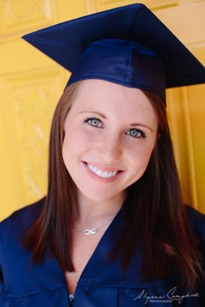 University of Arizona graduate in blue hat and robes in front of yellow door