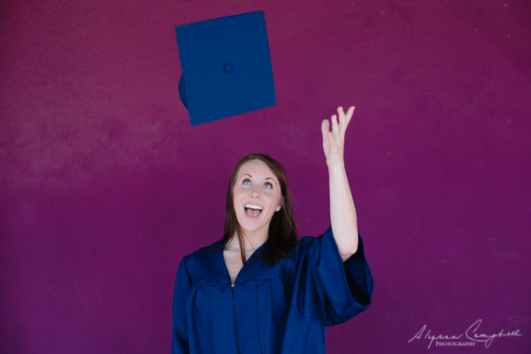 University of Arizona graduate throwing up hat in front of purple background