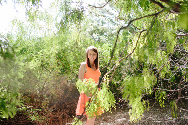 gorgeous brown haired college graduate with trees around her