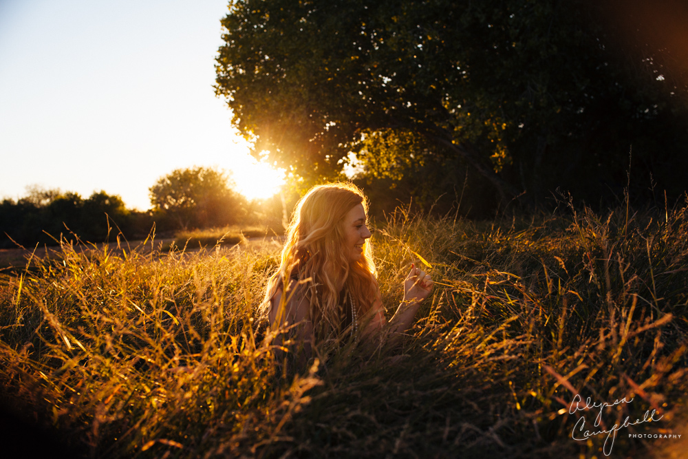 senior girl playing in field of grass at late sunset golden sun