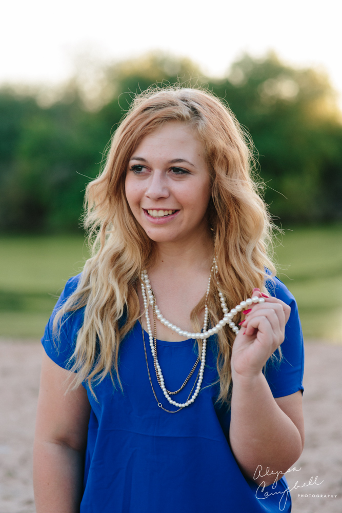 high school senior girl headshot playing with pearl necklace