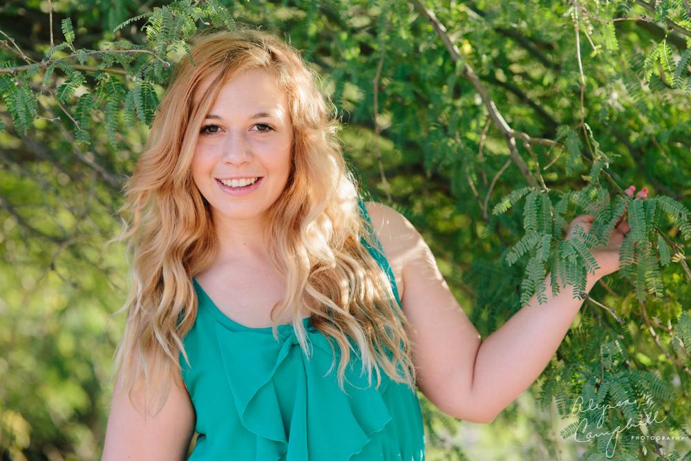 high school senior girl in front of green tree for senior portraits