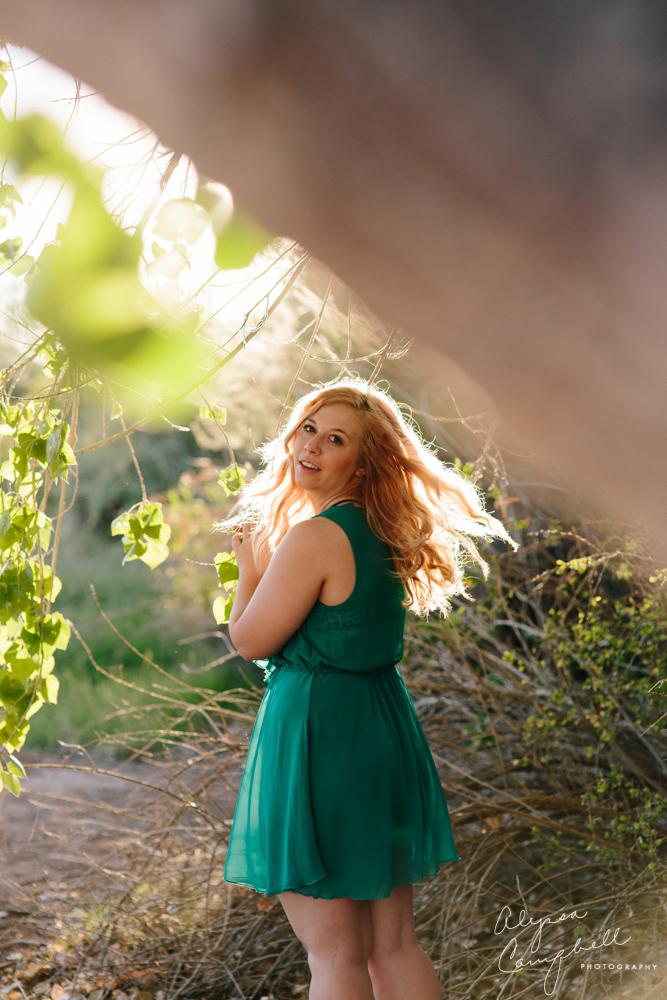 senior girl with blonde hair flying in sunlight