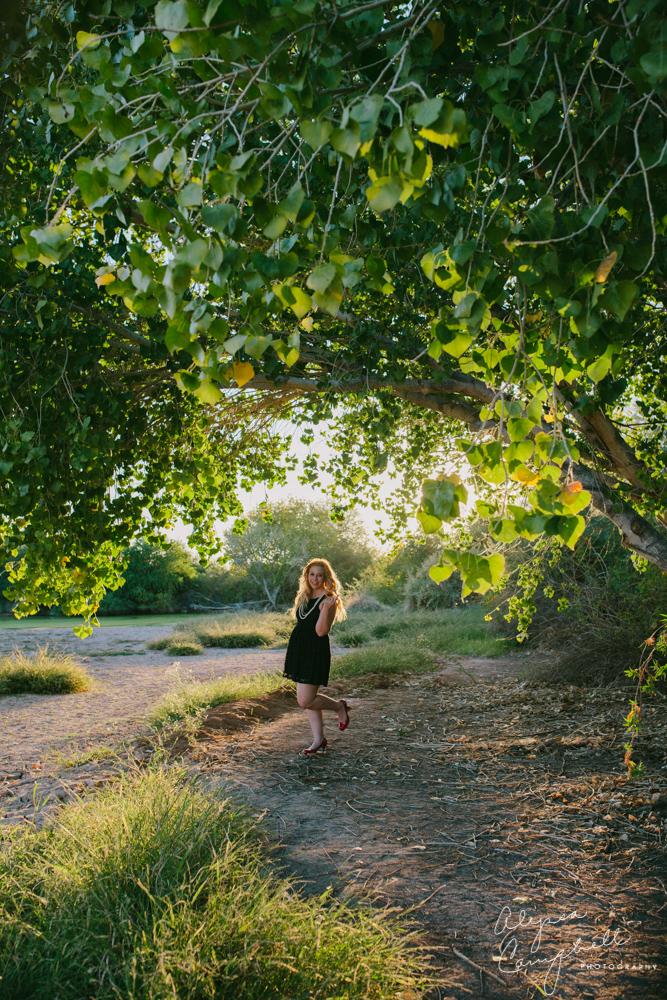 senior girl in black dress near green tree in arizona