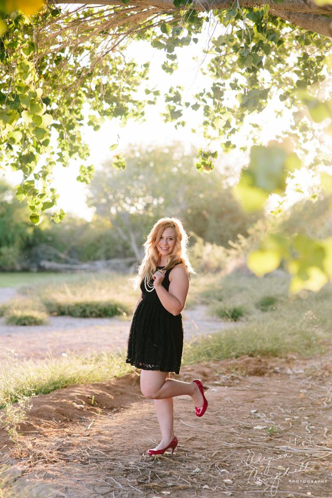 blonde high school senior girl playing with hair near tree in black dress heels
