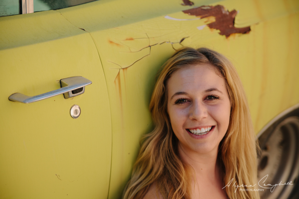 blonde high school senior girl against yellow old rusted car