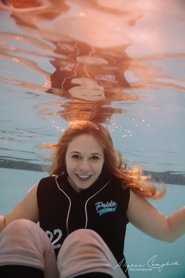 underwater senior photo in softball uniform in a pool