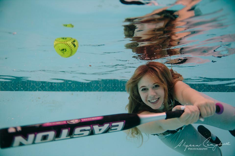 underwater senior photo of girl swinging softball bat in a pool