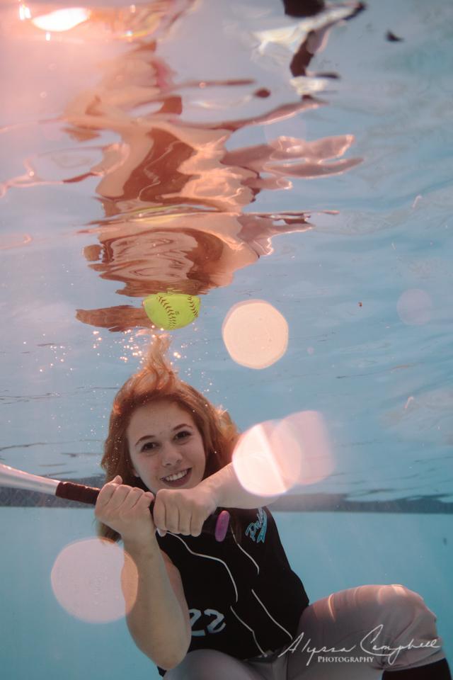 high school senior softball player swinging bat underwater