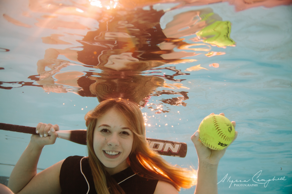 high school senior softball player holding bat and ball underwater in a pool