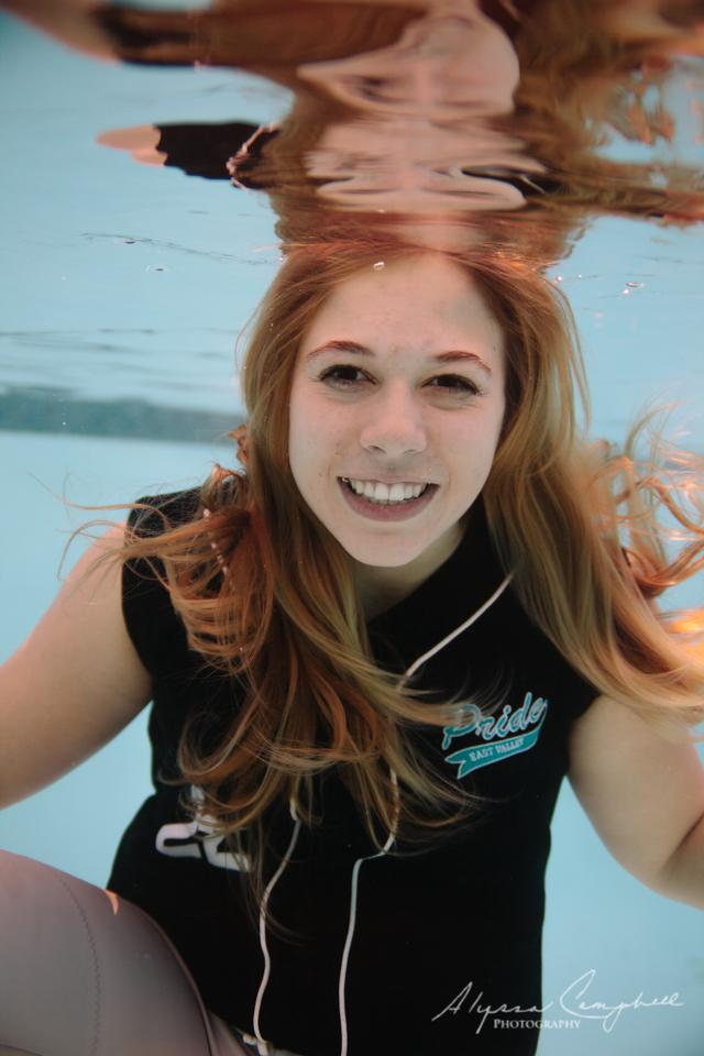 high school senior girl softball player in uniform underwater in pool in Arizona