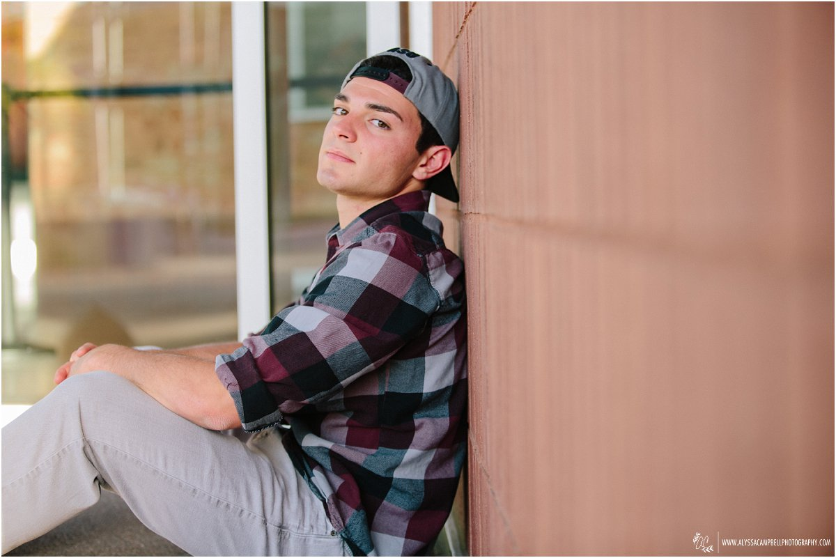 cool high school guy looking down brick wall with plaid shirt & hat on by Mesa AZ high school senior photographer Alyssa Campbell Photography