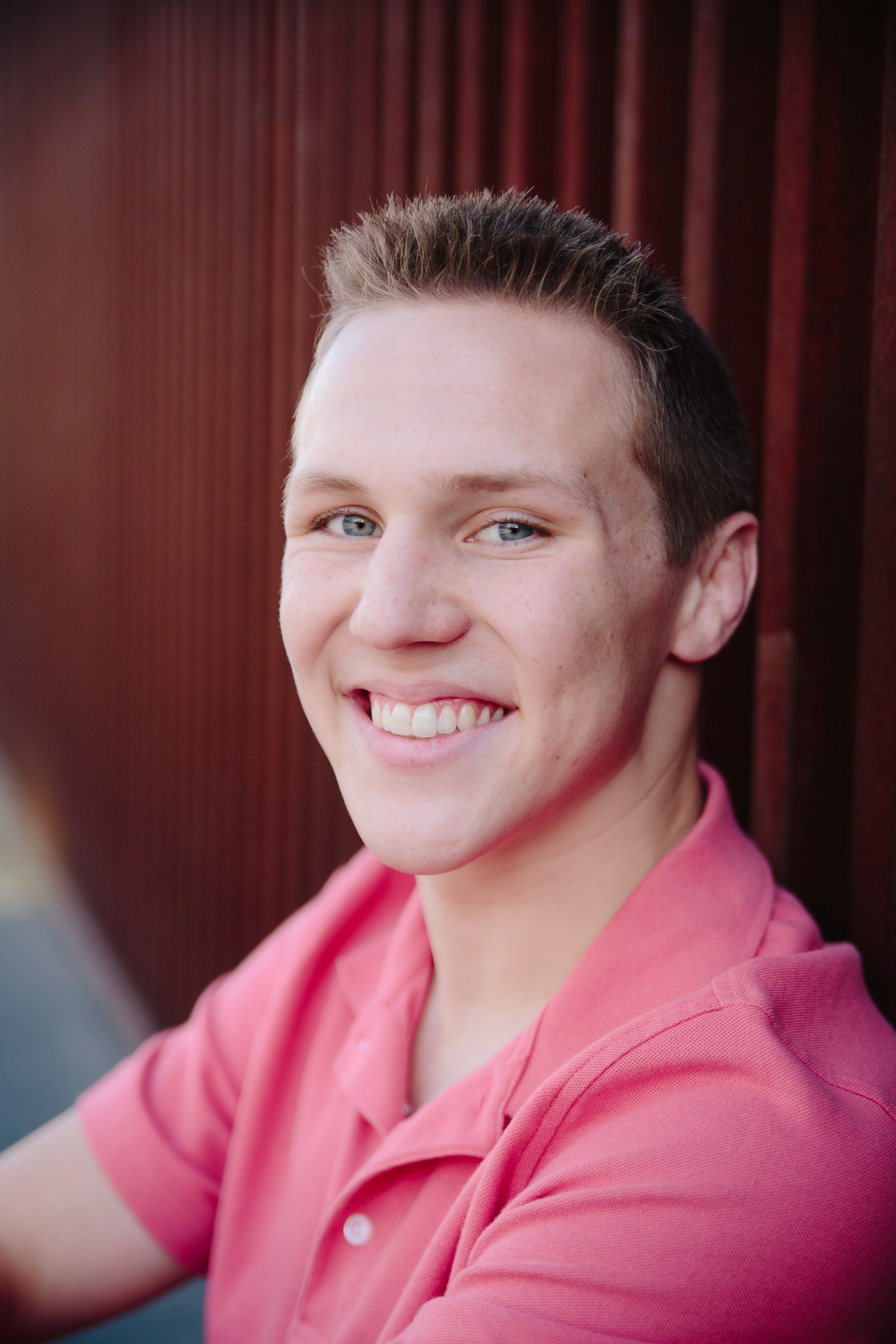 high school senior guy headshot in front of red rusty corrugated background