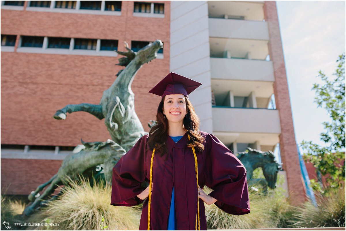 WP Carey Business School graduate portraits in front of horse statue in cap & gown College Senior photographer Alyssa Campbell